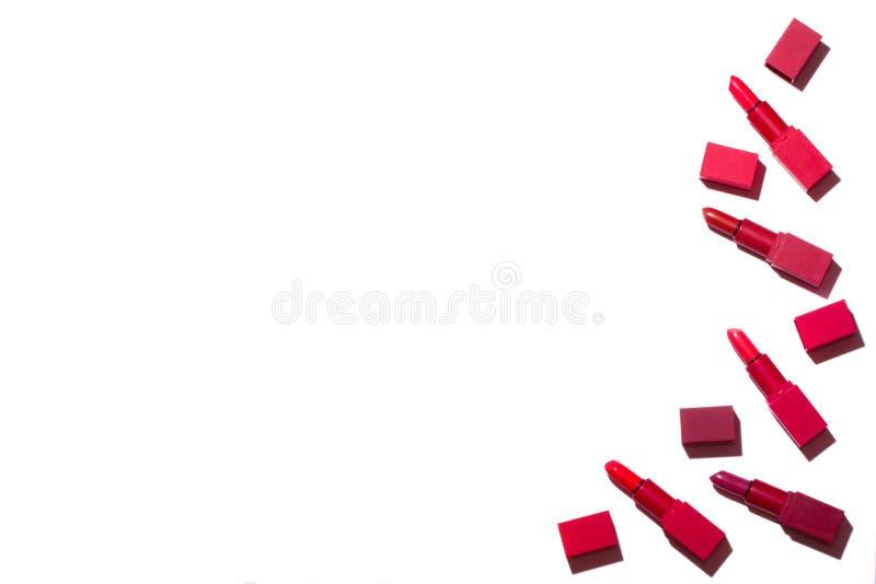 Groep rode die lippenstiften op een witte achtergrond worden uitgespreid royalty-vrije stock afbeeldingen