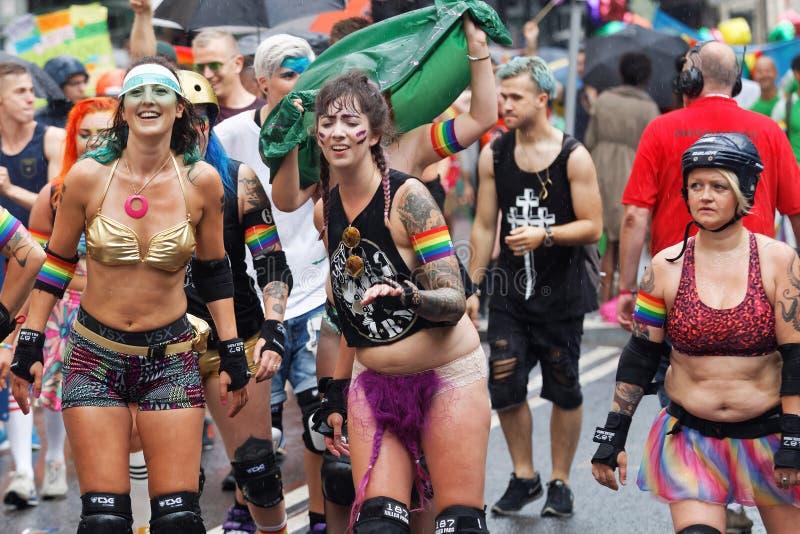 Groep rol schaatsende gelukkige meisjes in spectaculaire kleren stock fotografie