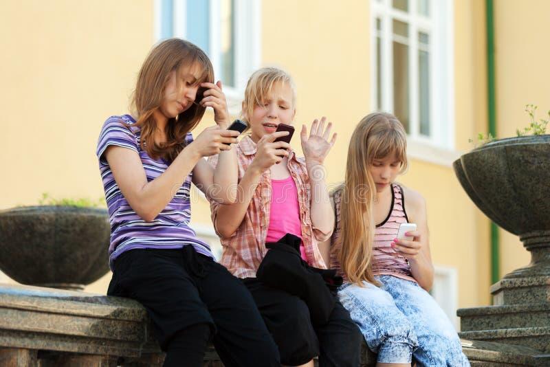 Groep schoolmeisjes die de celtelefoons uitnodigen royalty-vrije stock fotografie