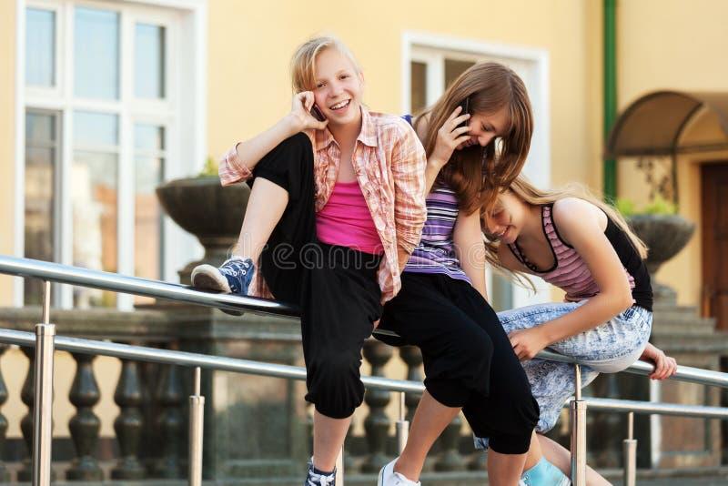 Groep schoolmeisjes die de celtelefoons uitnodigen stock foto