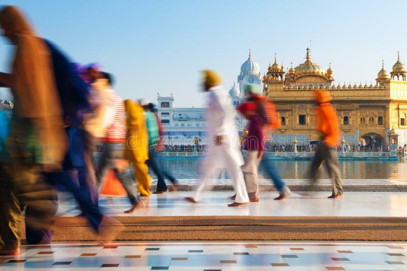 Groep Sikh pelgrims die door de Gouden Tempel lopen stock afbeelding