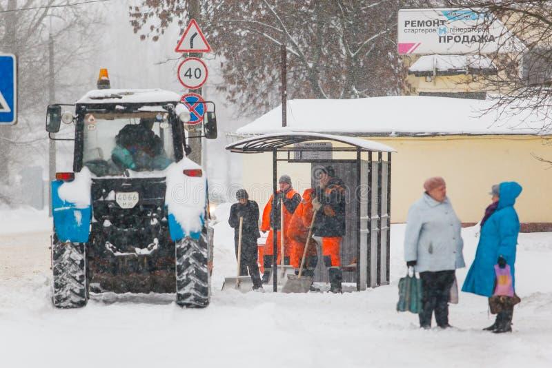 Groep straatreinigingsmachines in eenvormig wachten voor een tractor stock foto
