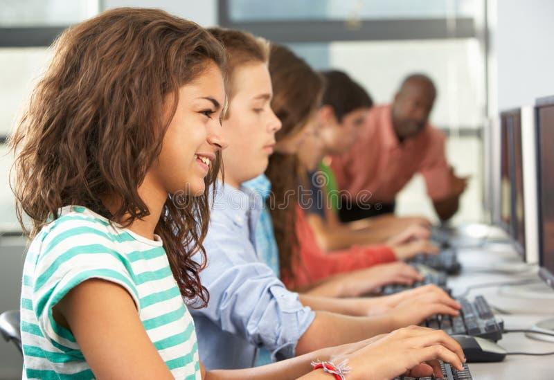 Groep Studenten die bij Computers in Klaslokaal werken stock afbeeldingen