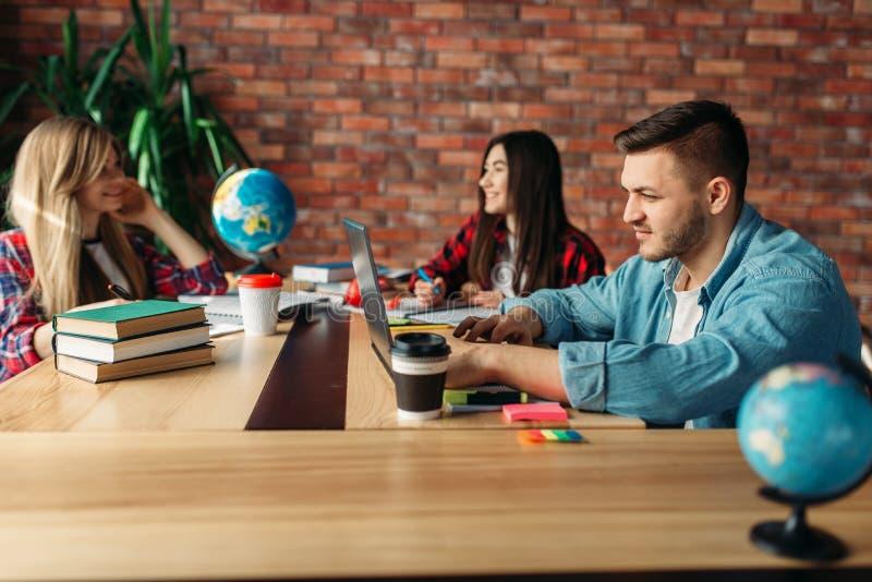 Groep studenten die bij de lijst samen bestuderen stock fotografie