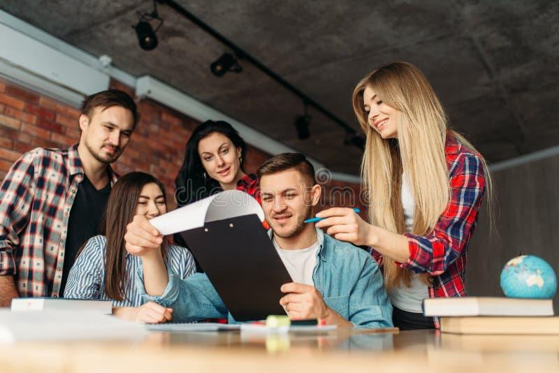 Groep studenten die op laptop samen kijken stock foto