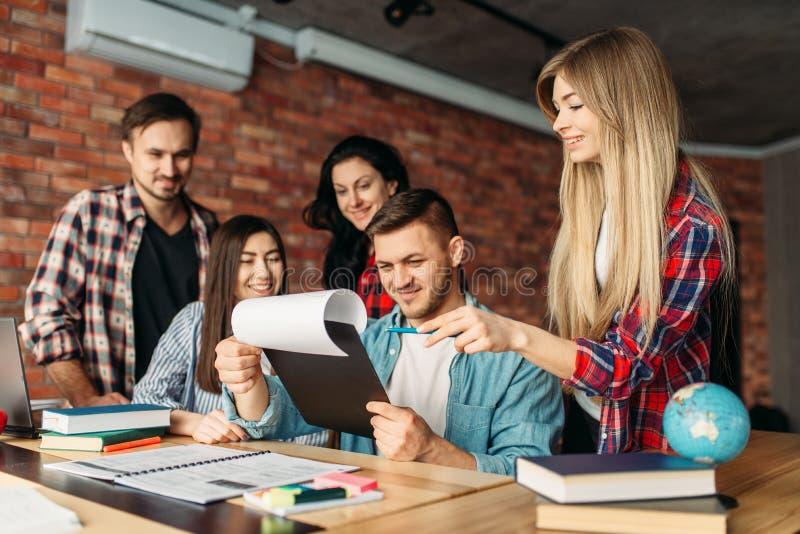 Groep studenten die op laptop samen kijken royalty-vrije stock fotografie
