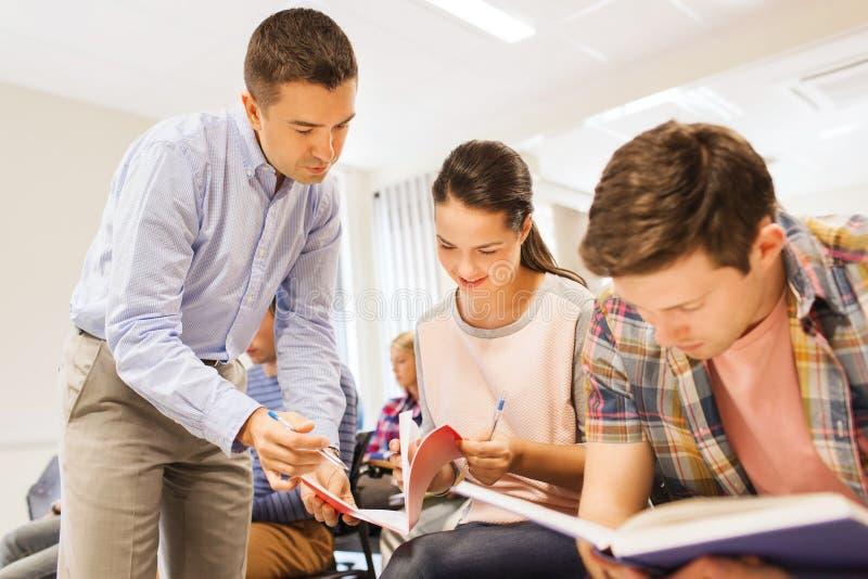 Groep studenten en leraar met notitieboekje stock foto's