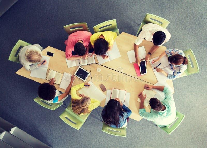 Groep studenten met tabletpc bij schoolbibliotheek royalty-vrije stock afbeelding