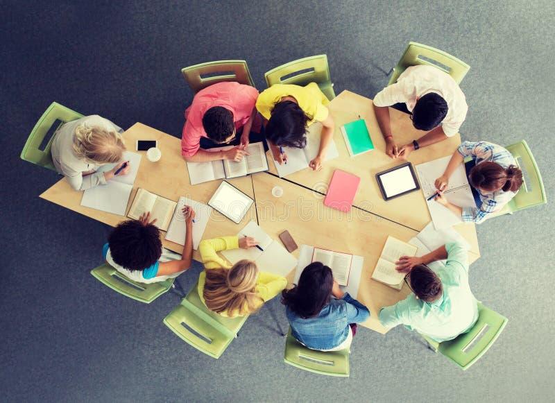 Groep studenten met tabletpc bij schoolbibliotheek stock foto's