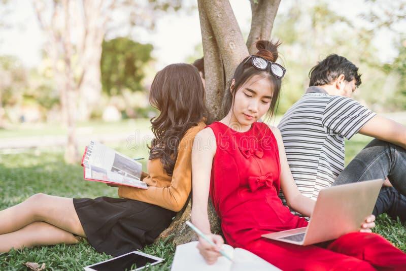 Groep studenten of tieners met laptop en tabletcomputers die uit hangen stock fotografie