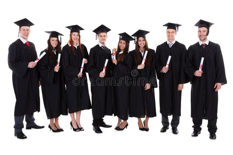 Groep studentengediplomeerden met hun diploma's royalty-vrije stock afbeelding