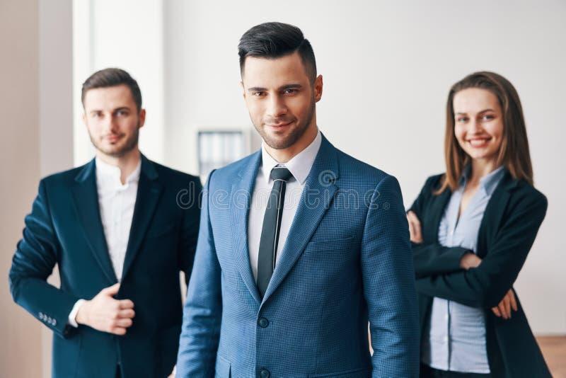 Groep succesvol commercieel team en hun mooie leider vooraan stock afbeelding