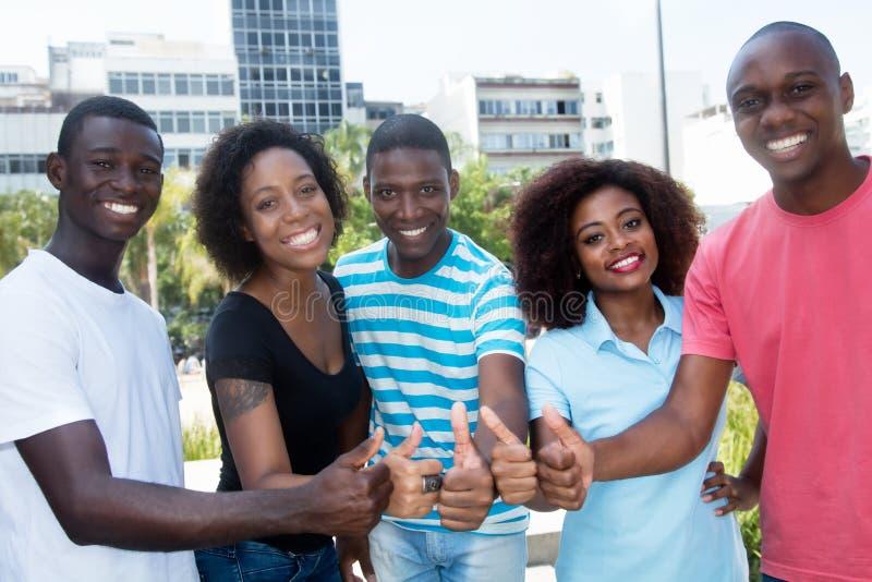Groep succesvolle Afrikaanse Amerikaanse mannen en vrouwen die duim tonen stock afbeelding