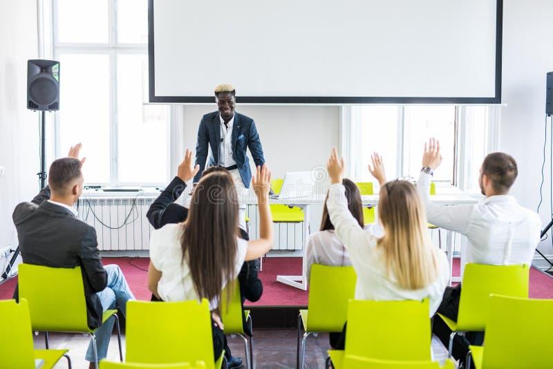 Groep succesvolle bedrijfsmensen bij de lezing die vragen stellen tijdens teamseminarie stock afbeelding