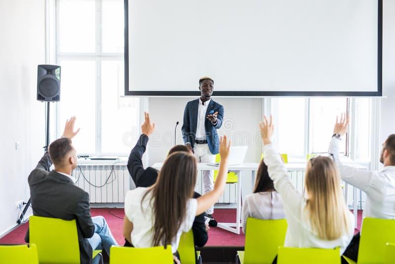 Groep succesvolle bedrijfsmensen bij de lezing die vragen stellen tijdens teamseminarie stock foto's