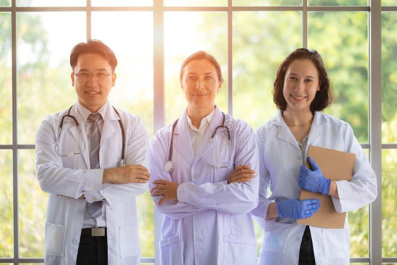 Groep thfee artsen die zich dichtbij groot venster met binnen erachter zonlicht bevinden Concept voor het teamwerk in het ziekenh royalty-vrije stock afbeeldingen