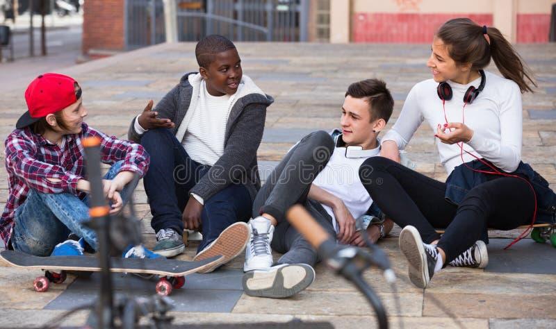 Groep tiener en vrienden die ontspannen babbelen stock foto's