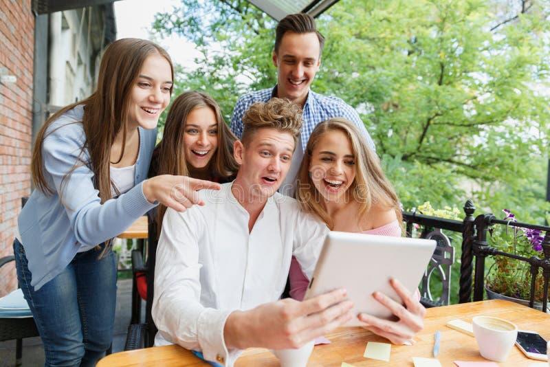 Groep tienerjaren die tablet op een koffieachtergrond gebruiken Gelukkige vrienden met tablet Modern levensstijlconcept stock foto's