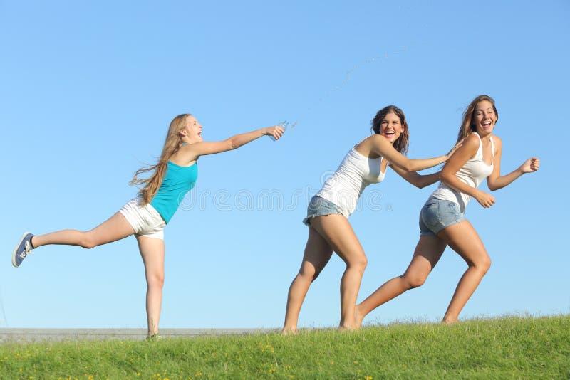 Groep tienermeisjes die werpend water spelen royalty-vrije stock afbeeldingen