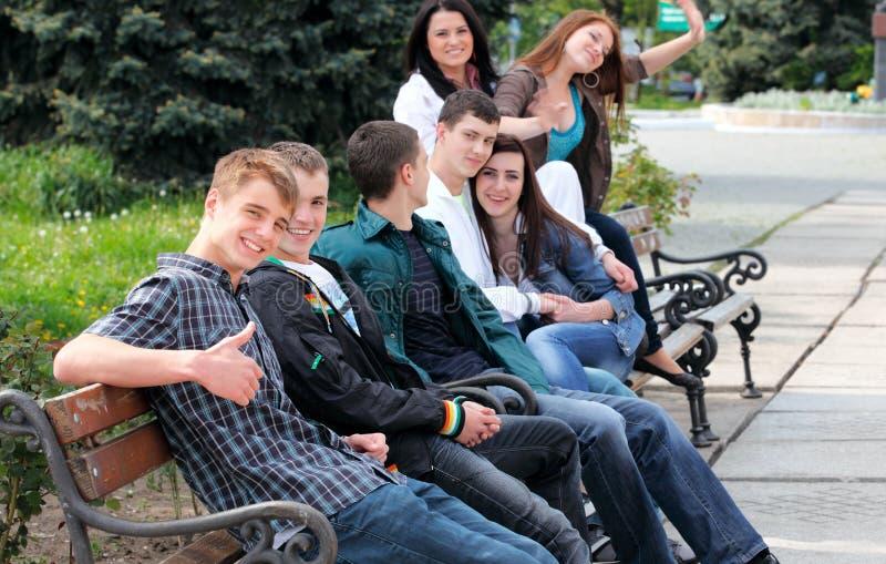 Groep tieners die buiten zitten stock afbeeldingen