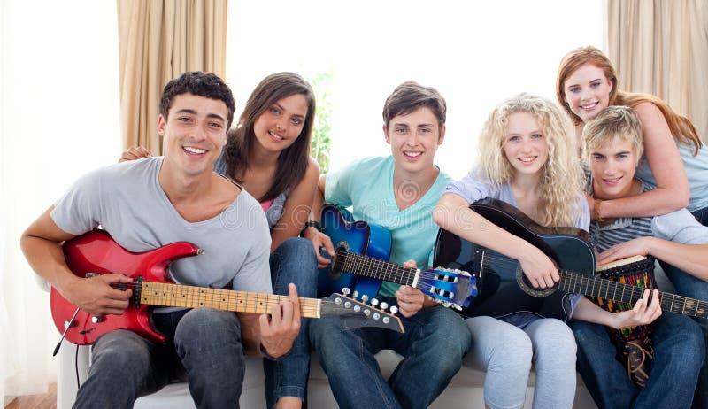 Groep tieners die gitaar thuis spelen stock foto