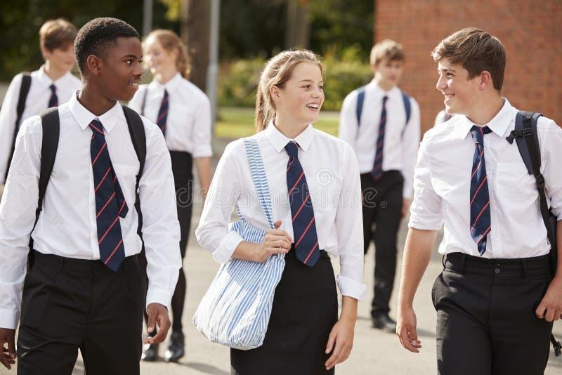 Groep Tienerstudenten in Eenvormige Buitenschoolgebouwen stock foto's