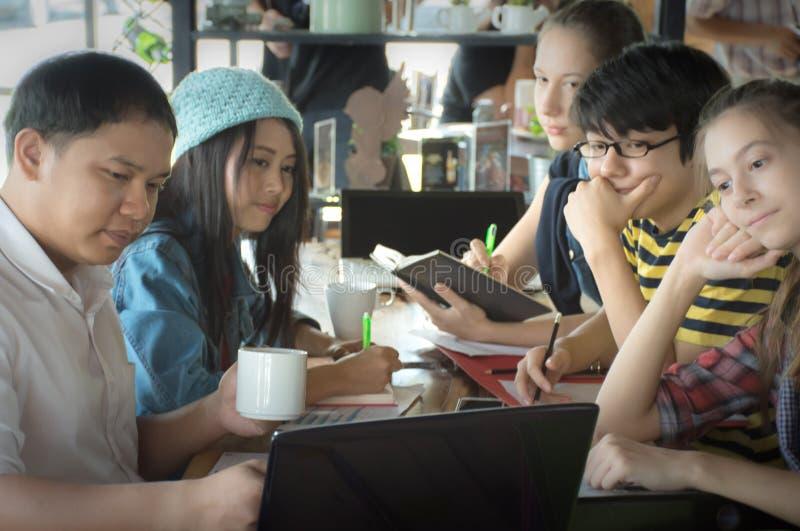 Groep tienervrienden die en in team met rapporten werken samenkomen royalty-vrije stock foto