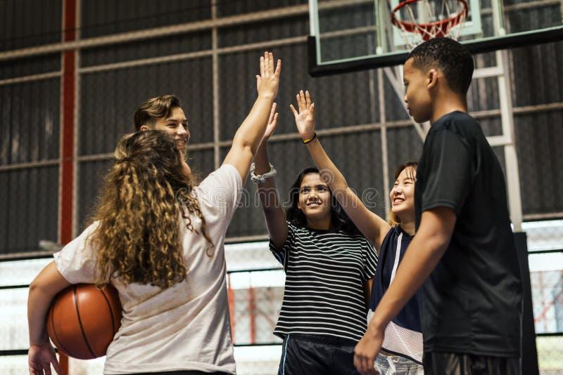 Groep tienervrienden op een basketbalhof die elkaar een hoogte vijf geven royalty-vrije stock fotografie