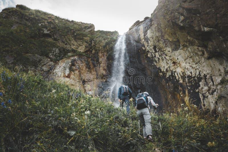 Groep Toeristen die bergop aan Waterval lopen Het Openluchtconcept van het reisavontuur stock foto's