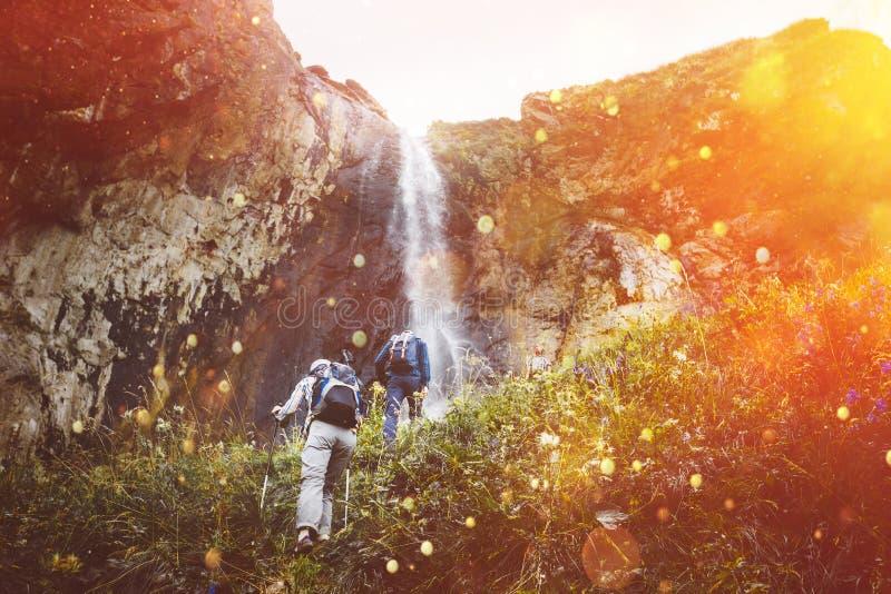 Groep toeristen die bergop aan Waterval met zonlicht lopen Het Openluchtconcept van het reisavontuur stock foto