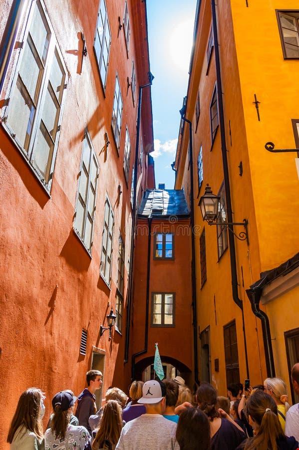 Groep toeristen die door comfortabele trillende smalle middeleeuwse straat met verbonden geeloranje rode gebouwenvoorgevels lopen royalty-vrije stock afbeeldingen