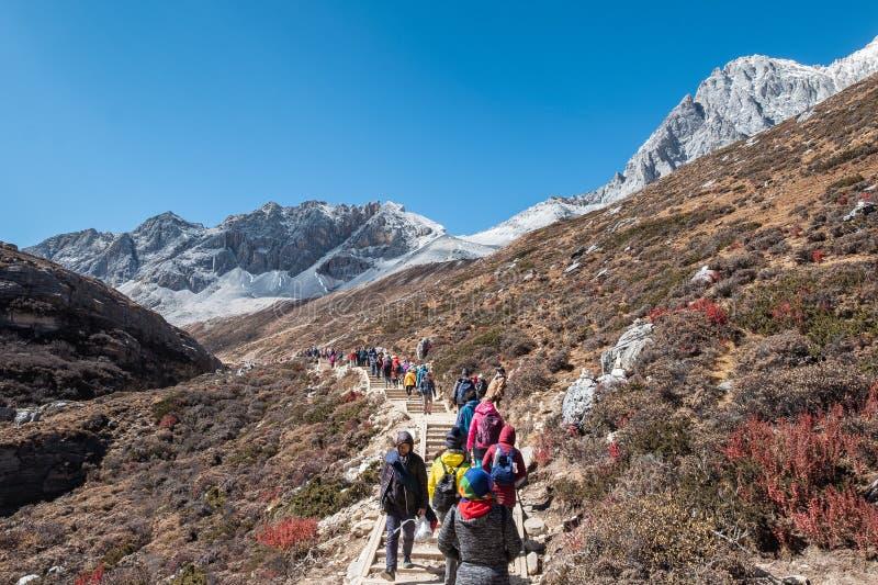 Groep toeristen die in heilige vallei dichtbij bij Melkmeer lopen, Yading-natuurreservaat royalty-vrije stock afbeeldingen