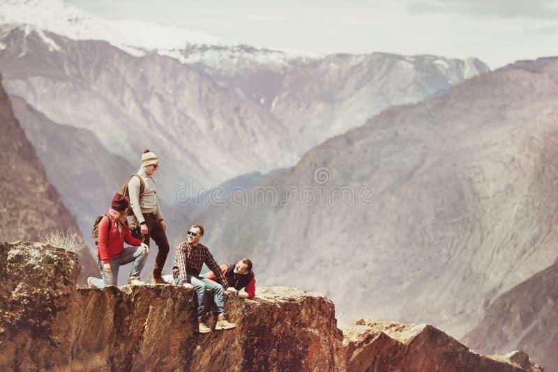 Groep toeristen op klip tegen bergen royalty-vrije stock afbeelding