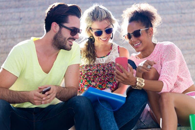 Groep universitaire studenten die mobiele telefoon in de straat met behulp van royalty-vrije stock afbeelding