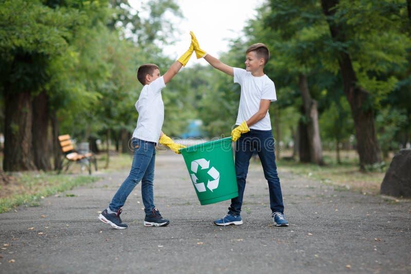 Groep van de het huisvuilinzameling van de jonge geitjes vrijwilligershulp de liefdadigheidsmilieu, selectieve zachte nadruk Het  royalty-vrije stock foto's