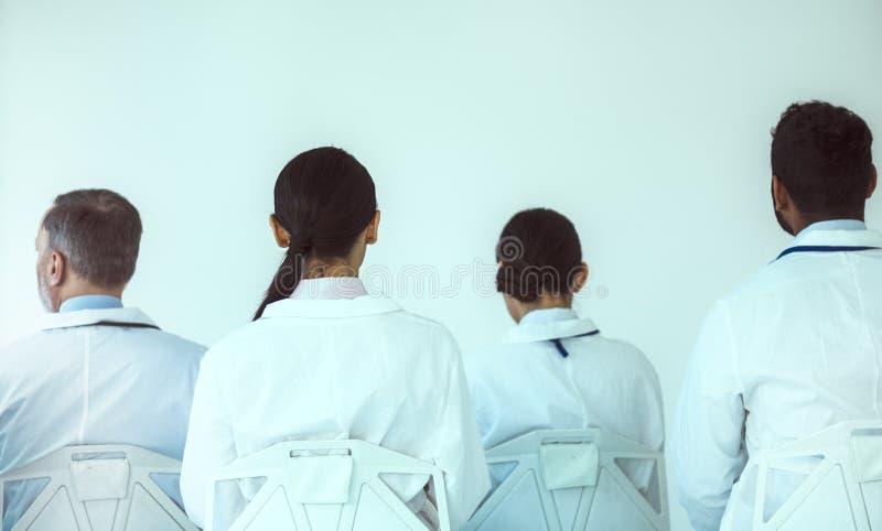 Groep van medisch werkers die voor de witte muur zitten royalty-vrije stock foto