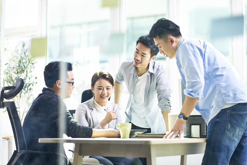 Groep van vier Aziatische teammates die samen het bespreken van zaken in bureau werken stock foto's