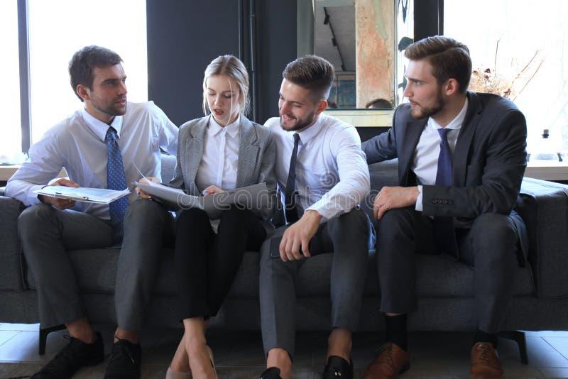 Groep van vier bedrijfsmensen die op bank zitten Zij konden niet gelukkiger zijn over het samenwerken stock foto