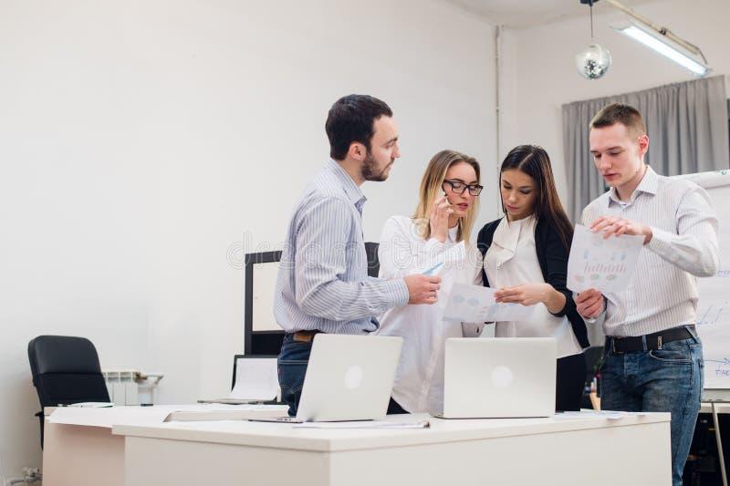Groep van vier diverse mannen en vrouwen in toevallige kleding die in bureau spreken royalty-vrije stock foto's