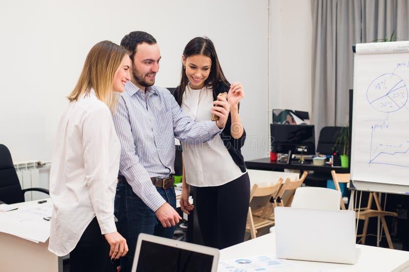 Groep van vier diverse vrolijke medewerkers die zelfportret nemen en grappige gebaren met handen maken op klein kantoor royalty-vrije stock fotografie