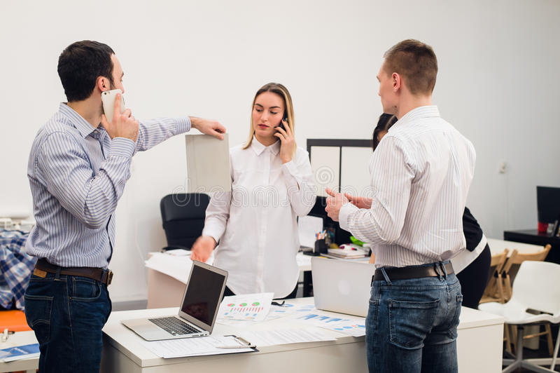 Groep van vier diverse vrolijke medewerkers die zelfportret nemen en grappige gebaren met handen maken op klein kantoor stock foto's