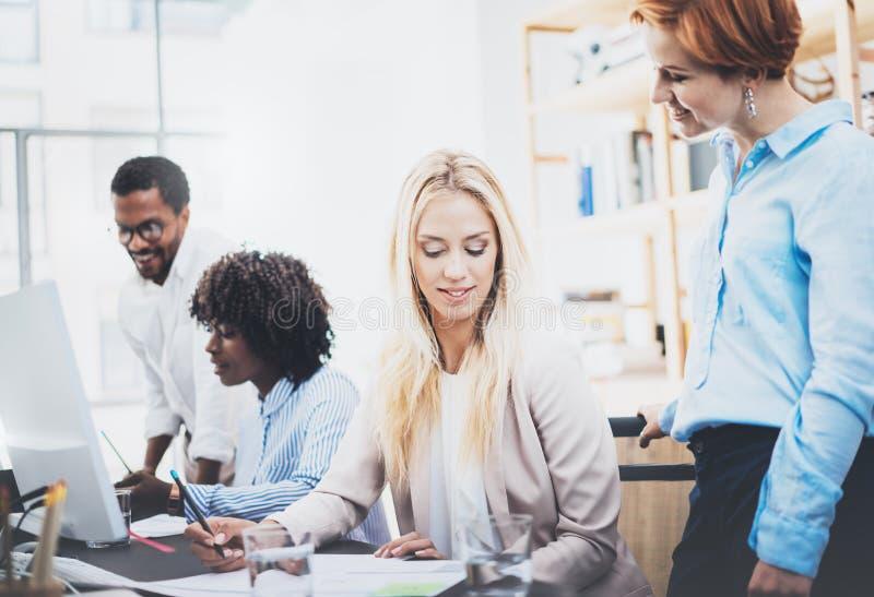 Groep van vier medewerkers die businessplannen in modern bureau bespreken Jongeren die grote ideeën maken Horizontaal, vaag backg royalty-vrije stock foto