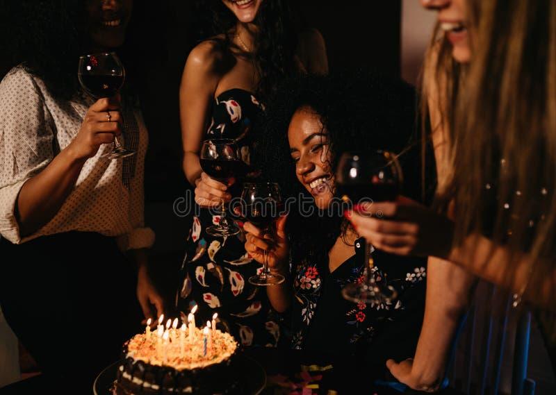 Groep van vier vrouwelijke vrienden die verjaardag thuis vieren stock foto's