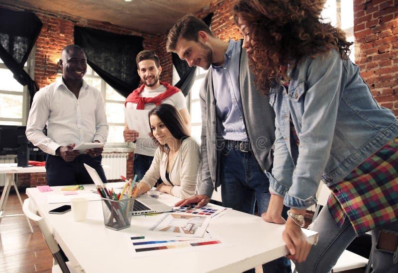 Groep van vijf creatieve arbeidersuitwisseling van ideeën samen in bureau, nieuwe stijl van werkruimte, gelukkige scène van mense stock afbeeldingen