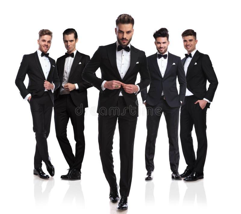 Groep van vijf elegante mensen met leider die kostuum dichtknopen royalty-vrije stock afbeeldingen