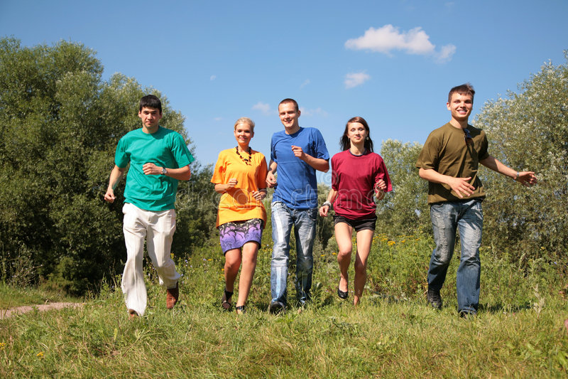 Groep van vijf vrienden in veelkleurige overhemdenlooppas royalty-vrije stock foto