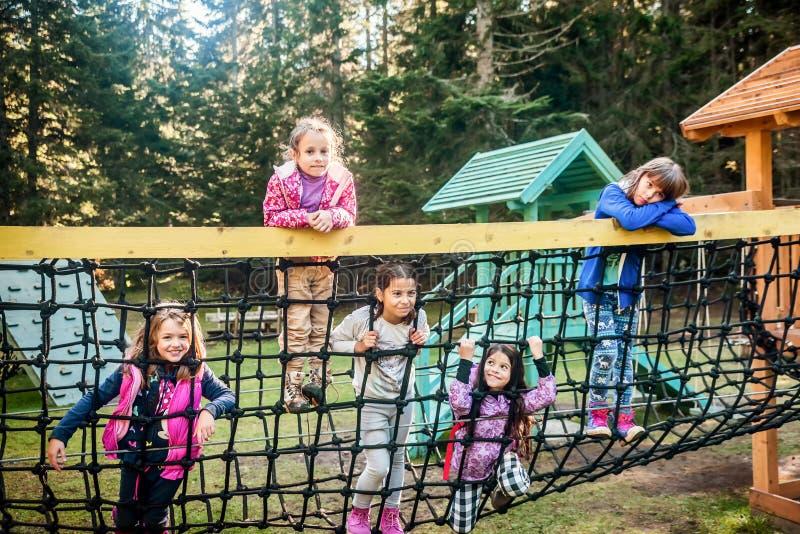 Groep van vijf vrouwelijke schoolvrienden die op de speelplaats spelen stock foto