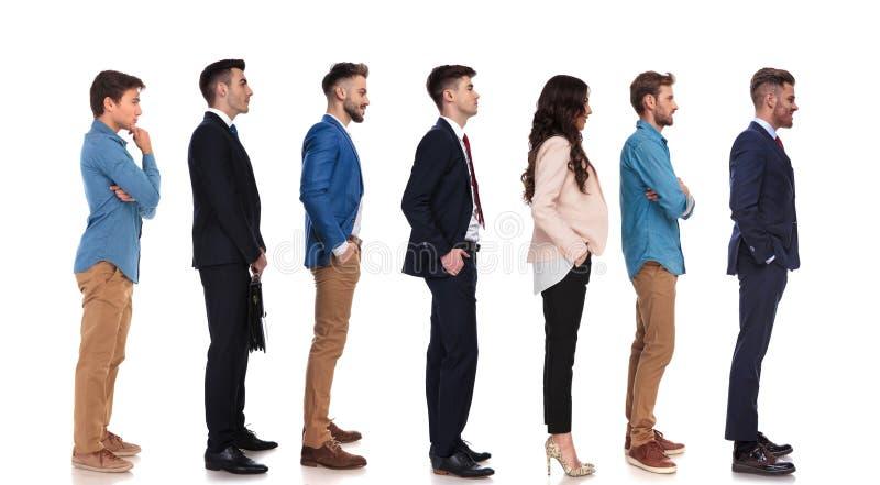 Groep van zeven mensen met verschillende reacties die in lijn wachten stock afbeelding
