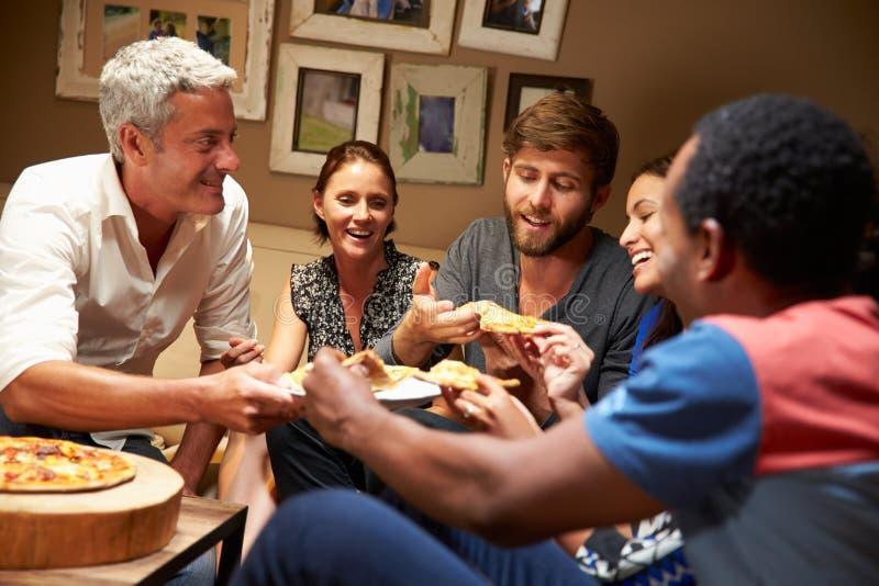 Groep volwassen vrienden die pizza eten bij een huispartij stock foto's