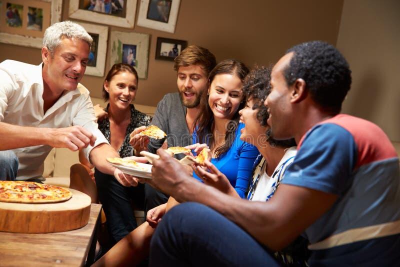 Groep volwassen vrienden die pizza eten bij een huispartij stock fotografie